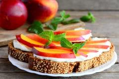 Frutti e panini del formaggio cremoso su un piatto e su una vecchia tavola di legno Panini del pane di segale con le nettarine ma Immagini Stock Libere da Diritti