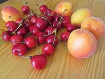 Frutti freschi di estate sulla tavola di legno leggera Albicocche e ciliege su fondo di legno Fotografia Stock