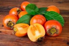 Frutti maturi del cachi dei cachi su fondo rustico Fotografia Stock