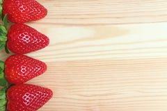 Frutti maturi freschi rossi vibranti della fragola allineati sulla Tabella di legno, con spazio libero per progettazione immagini stock