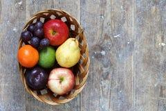 Frutti misti delle mele, della limetta, del limone, delle pere e delle prugne in ciotola di vimini Immagini Stock Libere da Diritti