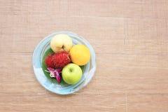 Frutti in piatto su fondo di legno Fotografia Stock Libera da Diritti