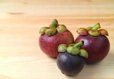 Frutti porpora maturi del mangostano di dimensione differente tre e di colore sulla Tabella di legno, con spazio libero per proge Immagine Stock Libera da Diritti