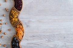 Frutti secchi in ciotole di legno sulla tavola con i dadi intorno Forma di Wave immagine stock libera da diritti