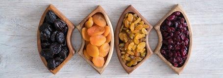 Frutti secchi in ciotole di legno sulla tavola Forma della farfalla immagini stock