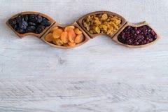 Frutti secchi in ciotole di legno sulla tavola Forma di Wave fotografie stock
