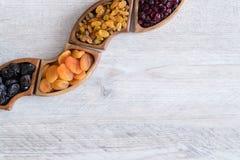 Frutti secchi in ciotole di legno sulla tavola Forma di Wave fotografia stock libera da diritti
