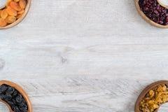 Frutti secchi in ciotole di legno sulla tavola Negli angoli fotografie stock