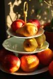 Frutti soleggiati delle arance delle mele delle pere di colore caldo sul server a tre livelli del supporto della porcellana accan Immagini Stock
