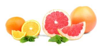 Frutti variopinti isolati su un fondo bianco Agrumi affettati con una struttura succosa Fogli di menta fresca Stile di vita sano Fotografia Stock Libera da Diritti