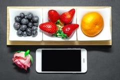 Fruttifica la fragola, il mirtillo e l'arancia con il telefono e sono aumentato Fotografia Stock Libera da Diritti