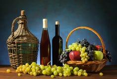 Fruttifichi in un canestro di vimini ed in un vino nella bottiglia Fotografia Stock