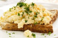 Förvanskade ägg på rostat bröd Arkivbilder