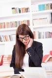 Förvirrad kvinnlig student med böcker Royaltyfria Bilder