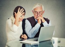 Förvirrad äldre man för kvinna undervisa hur man använder bärbara datorn Arkivfoton