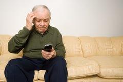Förvirrad äldre man med fjärrkontroll Arkivfoto
