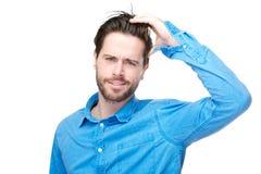 Förvirrad manlig individ med handen i hår Royaltyfria Foton