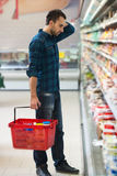 Förvirrad manshopping på supermarket Royaltyfria Bilder