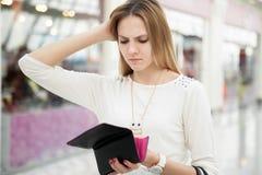 Förvirrad ung kvinna som kontrollerar hennes handväska, når att ha spenderat för mycket Royaltyfri Foto