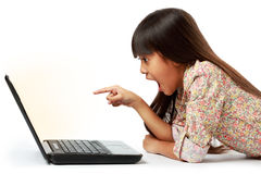 Förvånad flicka som pekar till datoren Arkivfoton
