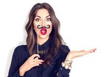 Förvånad flicka som rymmer den roliga mustaschen på pinnen Arkivbild