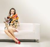 Förvånad kvinna med högen av skor Arkivfoton