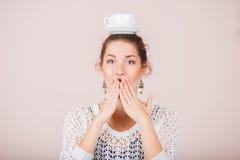 Förvånad kvinna med koppen och tefatet Royaltyfria Foton