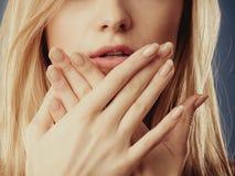 Förvånad kvinnaframsida som täcker hennes mun med händer Royaltyfria Bilder