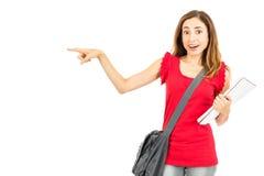 Förvånad kvinnlig student som pekar för att kopiera utrymme Royaltyfri Foto