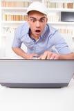 Förvånad man som pekar på datorbildskärmen med chock Arkivfoton