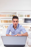 Förvånad student som ser den chockade bärbar datorbildskärmen Arkivbild
