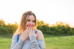 Förvånad ung kvinna med händer över henne utomhus- mun Arkivbilder