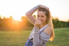 Förvånad ung kvinna med händer över henne utomhus- mun Arkivbild