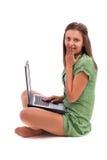Förvånadt ungt kvinnasammanträde däckar på med en bärbar dator Royaltyfri Foto