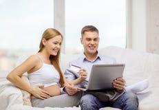 Förvänta familjen med bärbara datorn och kreditkorten Arkivbild