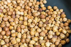 Fry hazelnuts in a frying pan. fresh nuts in the pan. royalty free stock photos