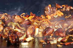 Fry onion carrot meat. Hot cook meat onion carrot vegetable in smoke fry on cauldron pan. The stage of cooking pilaf Stock Photography