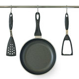 Fry pan and kitchen utensils hanging on a rail stock image