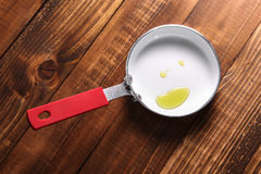 Fry pan with oil on wooden background Royalty Free Stock Image
