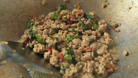Fry pork with basil in pan. Frying minced pork with cow-pea and basil , Thai food stock video footage
