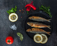 Fry sardines. roast, broi, grill fish on cast-iron frying pan with vegetables and spices around. Fry sardines. Omega 3. Fish with herbs. Mediterranean fish Stock Photos