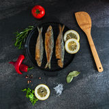 Fry sardines. roast, broi, grill fish on cast-iron frying pan with vegetables and spices around. Fry sardines. Omega 3. Fish with herbs. Mediterranean fish Stock Photography