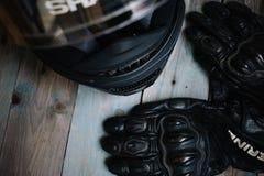 Fryazino, Rússia - 06 18 2018: acessórios do cavaleiro da motocicleta capacete e luvas na tabela de madeira, vista superior fotos de stock royalty free