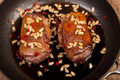 Fryed duck breast in frying pan with pine nuts and chili Stock Photo