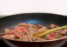 Frying beef in cast iron skillet royalty free stock photo