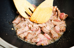Frying beef meat in sesame oil Stock Photos