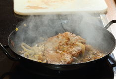 Frying beef and onions Stock Images