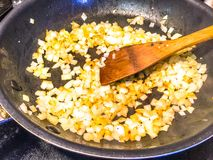 Frying Diced Onions. In skillet using a wooden spoon to stir them royalty free stock photography