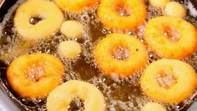 Frying donuts on hot oil stock video footage