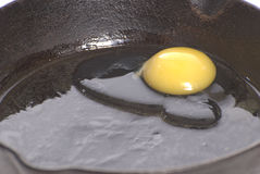 Frying Egg. Closeup view of a fresh egg frying in the bottom of a cast iron pan Stock Image